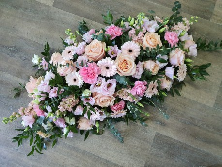 Pastel pinks and peaches casket spray