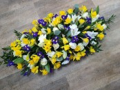 casket spray with added spring flowers